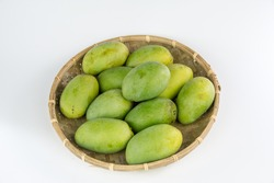mangos in a bamboo basket isolated on white background