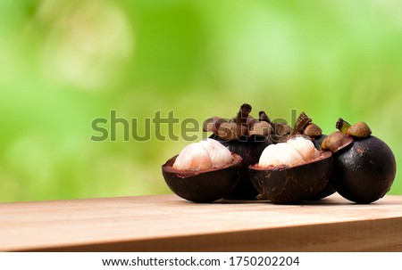 Mangosteen on the wooden table edge with blurred green forest as a background. Five mangosteens, two of them was peeled that reveal white flesh and the other that behind doen't peel. Queen of fruits. Stockfoto ©