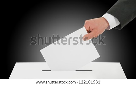 Manhand down ballot in the ballot box. Dark background.