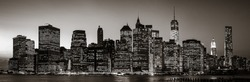 Manhattan at  night. Black and white image of New York City skyline panorama with lights and reflections.