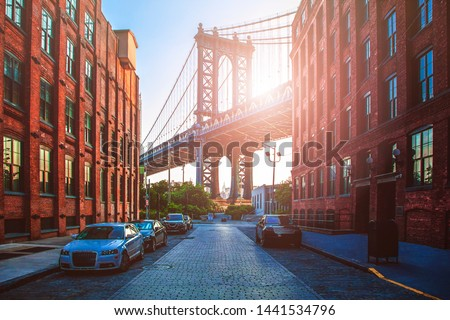 Manhattan Bridge between Manhattan and Brooklyn during sunset over East River with two brick buildings on a sunny day in Washington street in Dumbo, Brooklyn, NYC