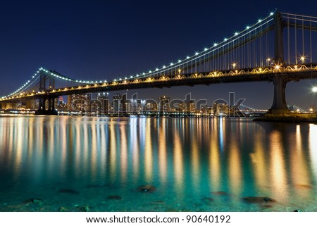 Manhattan Bridge, New York City. Manhattan Bridge with reflection of Manhattan skyline in East River.  Williamsburg Bridge in the background.