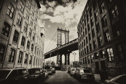 Manhattan bridge seen from a brick buildings in Brooklyn street in perspective, New York, USA. Business and travel background. Vintage, retro postcard with sepia filter.