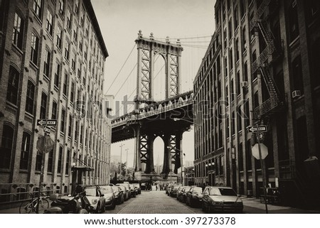 Manhattan bridge seen from a brick buildings in Brooklyn street in perspective, New York, USA. Business and travel background. Vintage, retro postcard with sepia filter. #397273378