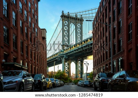 Manhattan bridge seen from a narrow alley enclosed by two brick buildings on a sunny day in summer  #1285474819