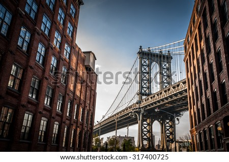 Manhattan bridge seen from a narrow alley enclosed by two brick buildings on a sunny day in summer #317400725