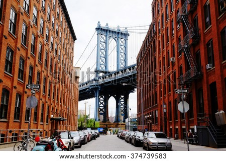 Manhattan bridge seen from a red brick buildings in Brooklyn street in perspective, New York, USA. Beautiful classic apartments in New York City. Beautiful american street. Famous view. #374739583