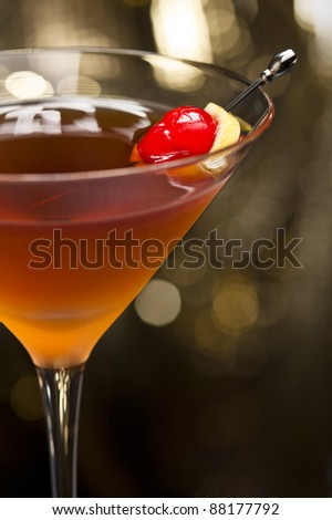 Manhattan cocktail garnished with a cherry and lemon and gold glitter back ground