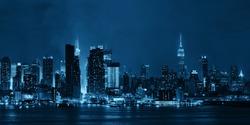 Manhattan midtown skyscrapers and New York City skyline panorama at night with fog