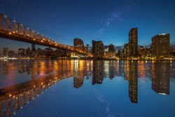 Manhattan panorama at dusk as seen from Roosevelt Island in New York, USA. New York night scene with East River waterfront illuminated buildings and starry sky with milkyway.