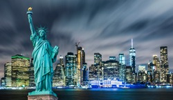 Manhattan panoramic skyline at night. Statue of Liberty with Manhattan background. New York City, USA.
