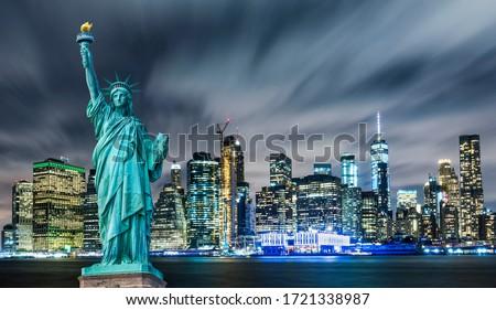 Manhattan panoramic skyline at night. Statue of Liberty with Manhattan background. New York City, USA.