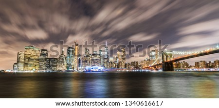 Manhattan panoramic skyline at night with Brooklyn Bridge. New York City, USA. Office buildings and skyscrapers at Lower Manhattan (Downtown Manhattan). #1340616617