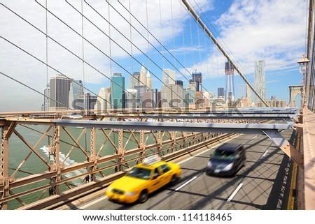 Manhattan skyline and taxi cab crossing Brooklyn Bridge, New York