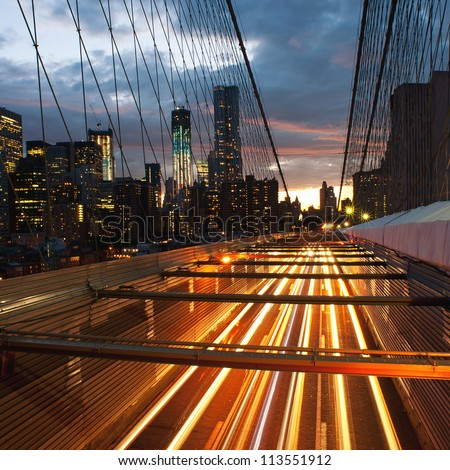 Manhattan skyline from the Brooklyn bridge at dusk with cars trail.