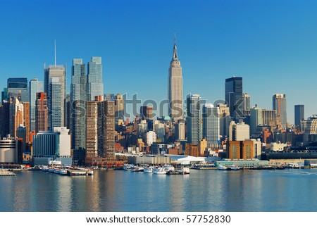 Manhattan Skyline with Empire State Building, New York City over Hudson River with boat and pier.