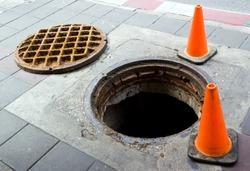 Manhole cover open on the foot bath near street