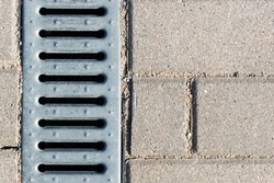 Manhole on concrete drain system cover. Urban sewer background. Metal drain cover texture. Pavement water drainage system. Vertical silver color metal grid.