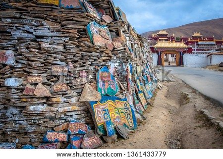 """Mani Stones wall carved Tibetan Buddhist mantra """"Om Mani Padme Hum (Translation : 'Praise to the Jewel in Lotus')"""" at front of Litang Monastery, Garze Tibetan Autonomous Prefecture, Sichuan, China."""
