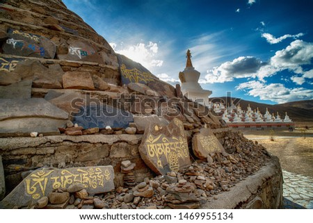 """Mani Stones wall carved Tibetan Buddhist mantra """"Om Mani Padme Hum (Translation : 'Praise to the Jewel in Lotus')"""" at front of Tibetan White Pagoda in Daocheng,China"""