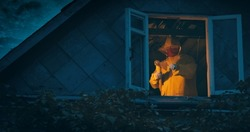 Maniac in a yellow raincoat with an axe and a knife on the top floor of an old house. The concept of horror, thriller and Halloween holiday. At night, the camera shoots outside through the window
