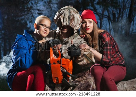 Maniac with the chainsaw dressed in a dirty bloody raincoat is sitting with the victim.