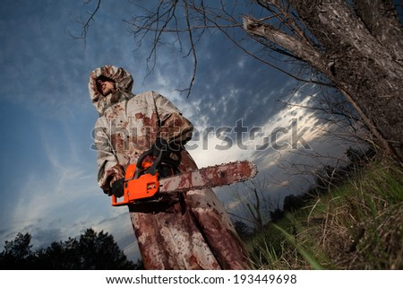 Maniac with the chainsaw dressed in a dirty bloody raincoat. Sunset forest on the background