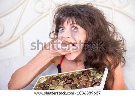 Manic mature woman crying and eating chocolates in her bedroom
