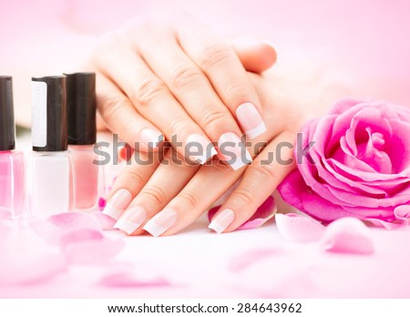 Manicure and Hands Spa. Beautiful Woman hands closeup. Manicured nails and Soft skin. Beauty hands with rose flower petals. Beauty treatment. Beautiful woman\'s nails with beautiful french manicure