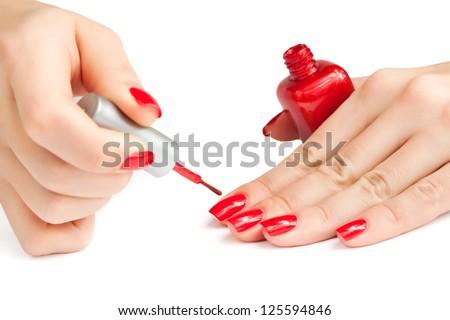 manicure. applying red nail polish