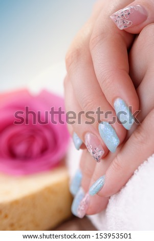 Manicure - Beautiful manicured woman\'s fingernails with glitter blue nail polish and nail art on some fingers. Studio shot. Selective focus.