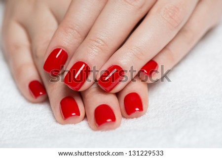 Manicure - Beautiful manicured woman\'s hands with red nail polish on soft white towel.
