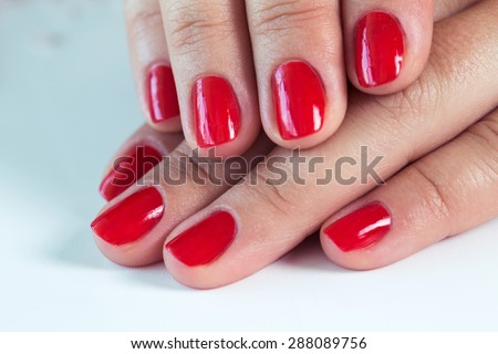 Manicure - Beautiful manicured woman\'s hands with red nail polish on soft white towel