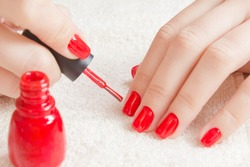 Manicure - Beautiful manicured woman's nails with red nail polish on soft white towel.