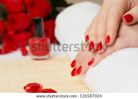 Manicure - Beautiful manicured woman\'s nails with red nail polish on soft white towel.