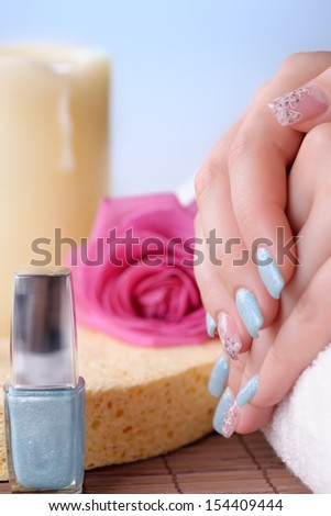 Manicure - Beautifully manicured woman\'s fingernails with glitter blue nail polish and nail art on fourth fingers. Studio shot. Selective focus.