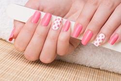 Manicure - Beauty treatment photo of nice manicured woman fingernails holding nail file. Feminine nail art with nice glitter, pink and white nail polish.