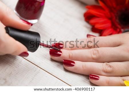 Manicure - Beauty treatment photo of nice manicured woman fingernails on a white wooden desk decorated with flowers. Selective focus.