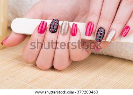 Manicure - Beauty treatment photo of nice manicured woman fingernails. Very nice feminine nail art with nice pink, gold and black nail polish.