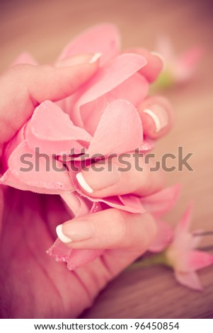 manicure, hand with French nailtips holding flower