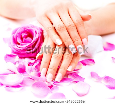 Manicure, Hands spa. Beautiful female hands, soft skin, beautiful nails with pink rose flowers petals. Healthy Woman hands. Beauty salon. Treatment. Beautiful woman\'s nails with french manicure