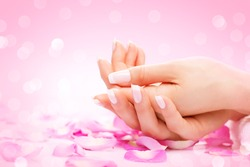 Manicure, Hands spa Beautiful woman hands, soft skin, beautiful nails with pink rose flowers petals. Healthy Woman hands. Beauty salon. Beauty treatment.  Female nails with beautiful french manicure