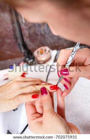 Manicure in progress - Beautiful manicured woman's nails with red nail polish. The industry of beauty and nail care, beauty salons #702075931