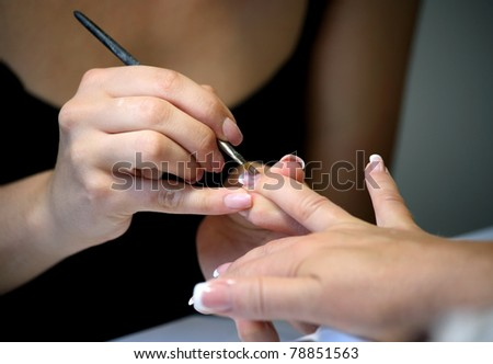Manicure making female hands covering of pink enamel, macro