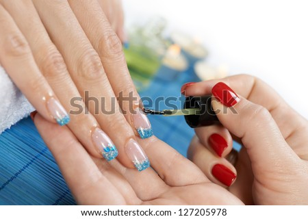 Manicure - manicure treatment, applying cuticle oil on woman nails with very interesting nail art.