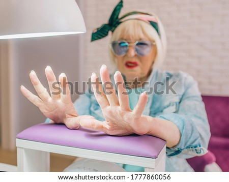 manicure master in blue gloves creaming hands of elderly stylish woman in blue sunglasses and jeans jacket sitting at manicure salon (studio) not happy with her nails. Treatment, care, anti age, manic
