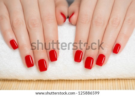 Manicure - nice manicured woman nails with red nail polish