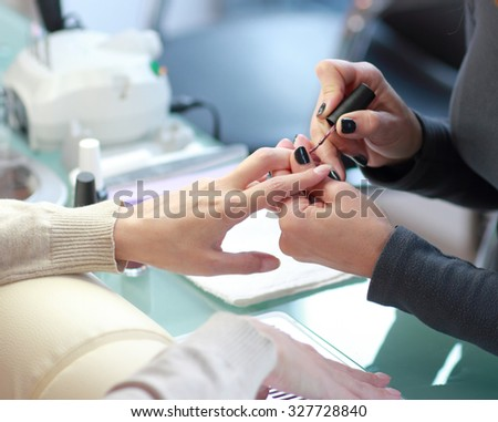 Manicure. Processing of nails by a nail file .Focus on the one hand and the customer master