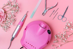 Manicure tools and drill on pink background, top view.