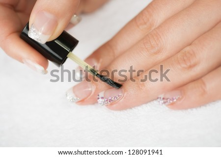 Manicure treatment - Manicure treatment, applying cuticle oil on woman nails.